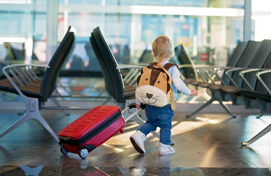 Barn på flyplass med trillekoffert