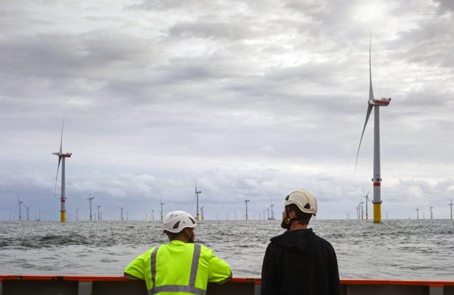 To personer ser utover vindmøllepark til havs.