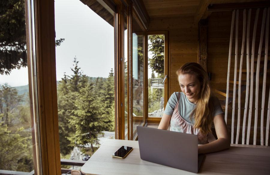 Illustrasjonsbilde av kvinne på hytte med laptop